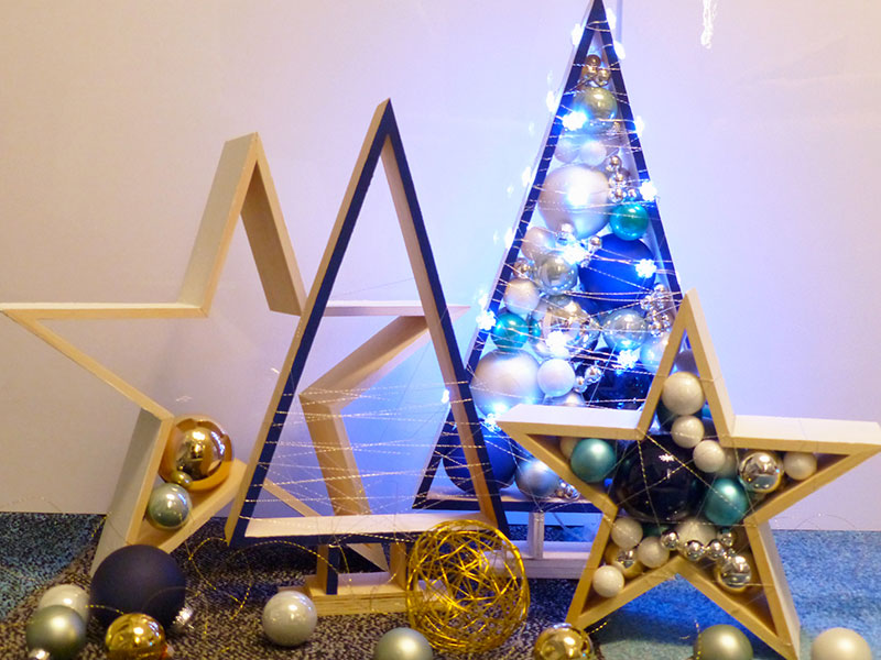 Tannenbäume und Sterne aus Holz gefüllt mit Weihnachtskugeln und anderen Dekoelementen