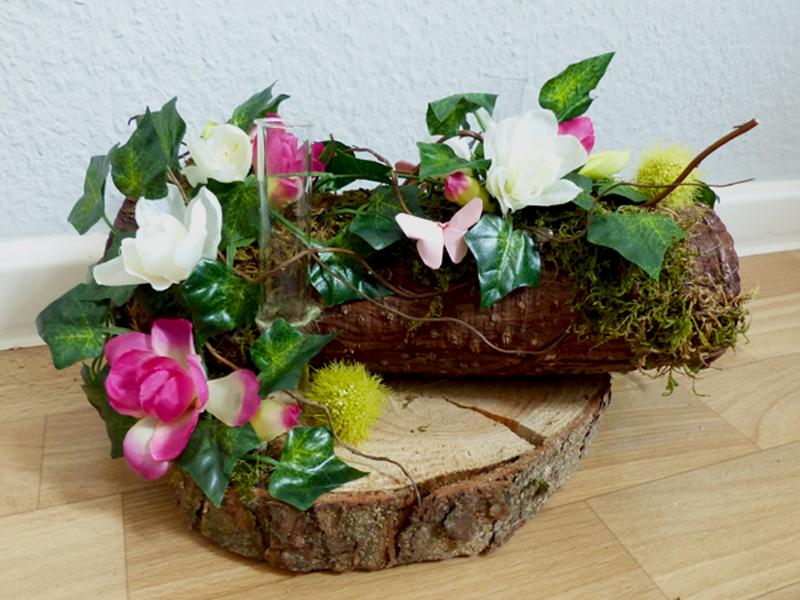 Baumstamm mit floraler Dekoration und Reagenzgläsern zur Bestückung mit Naturblumen