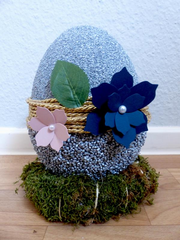 Kleines silbernes Ei (21 cm) verziert mit goldener Kordel und Blüten