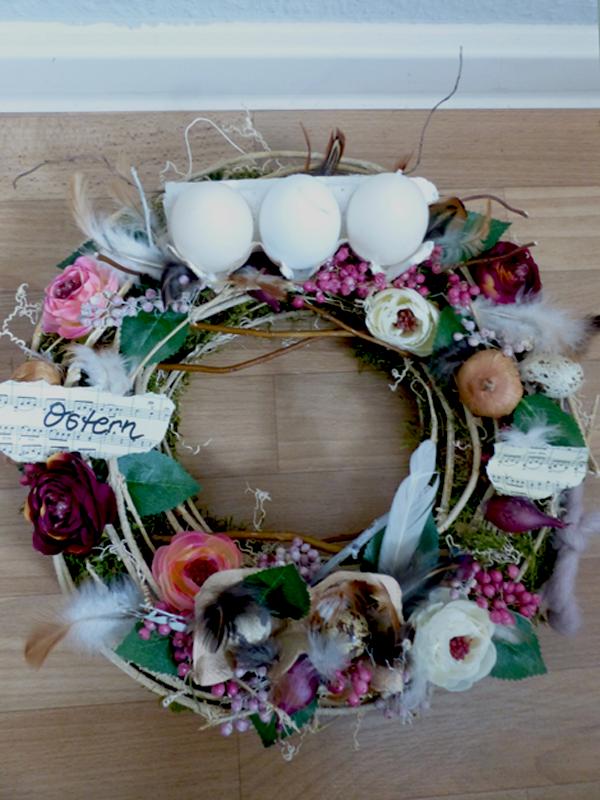 Kranz mit Eierpappen, Kerzen und floraler Dekoration in Frühlingstönen