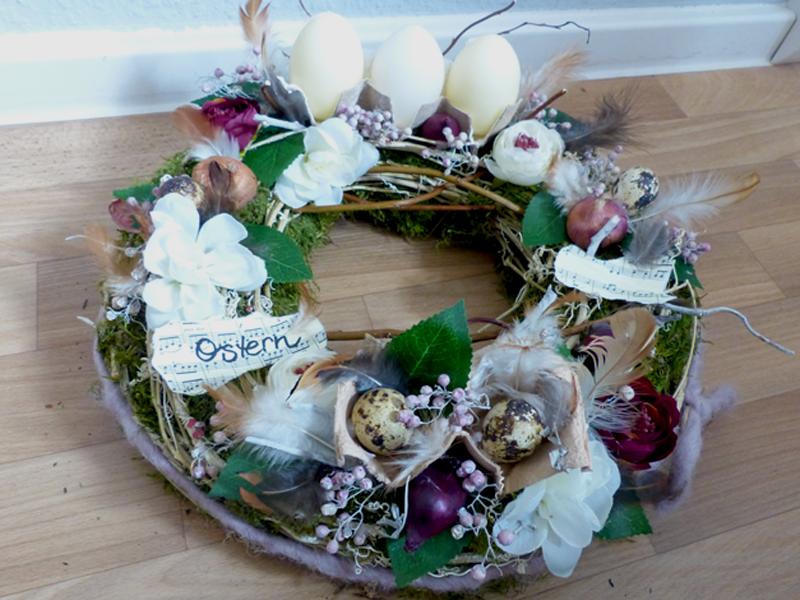 Kranz mit Eierpappen, Kerzen und floraler Dekoration in dezenten Tönen
