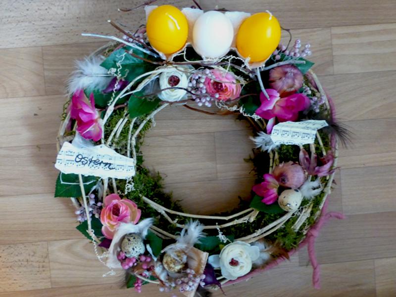 Kranz mit Eierpappen, Kerzen und floraler Dekoration in kräftigeren Tönen